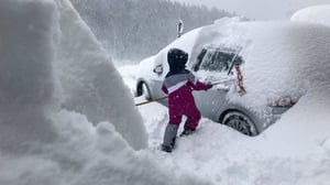 A boy clears a car window of snow in Salzburg, Austria as new snow falls