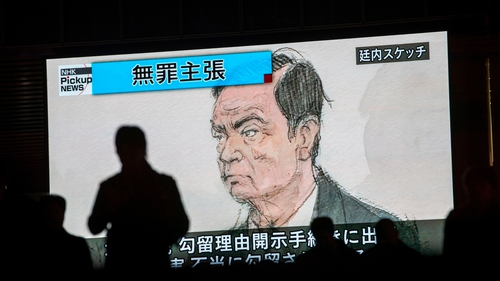 Japanese pedestrians pass by a TV screen displaying a sketch of former Nissan chairman Carlos Ghosn in court earlier this week