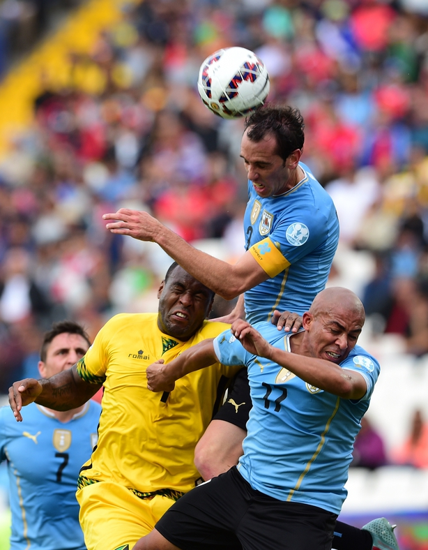 Romeo Parkes battling for possession with Uruguay's Diego Godin
