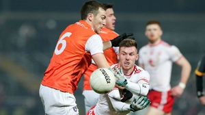 Tyrone's Declan McClure gets off  a handpass under pressure form Brendan Donaghy of Armagh