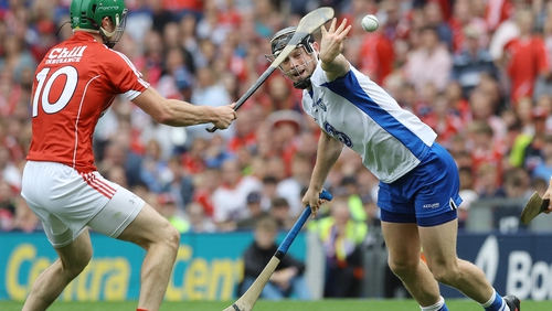 Philip Mahony of Waterford hand passes the ball away from Cork's Seamus Harnedy