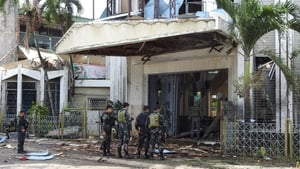 Police officers and soldiers stand outside the bomb-hit church in Jolo, Sulu province