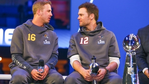 New England Patriots quarterback Tom Brady (12) and Los Angeles Rams quarterback Jared Goff (16) sit beside the Vince Lombardi Trophy