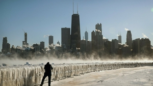 A man takes a picture along the frozen lakefront in Chicago