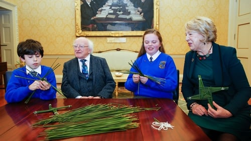Oisín Lee and Sophie Hannon from St Brigid's Primary School, Kildare make St Brigid's crosses for President Michael D Higgins and Sabina Higgins at Áras An Uachtaráin. Photo: Kenneth O'Halloran