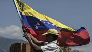 A Venezuelan man holds a flag during a protest against Nicolas Maduro's government in Caracas