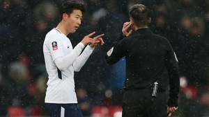 Spurs' Heung-Min Son asks a referee for a VAR review in last season's FA Cup