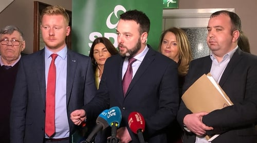 SDLP leader Colum Eastwood (centre) speaks to the media after the vote