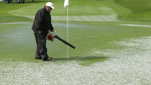 A member of the ground staff clears hail form the first green