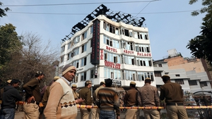 Locals and police on the scene at the hotel where a fire broke out in New Delhi