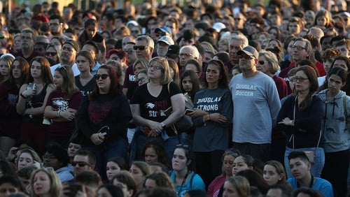 People attend a memorial service at Pine Trails Park for the victims of the mass shooting