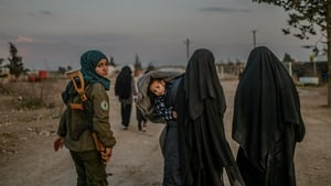 Wives of IS fighters walk under the supervision of a female fighter from the SDF in northeastern Syria