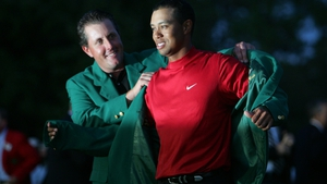 Phil Mickelson helps Tiger Woods into the green jacket after his Masters play-off victory in 2005