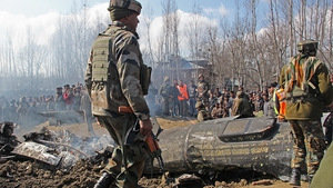 Indian army and locals stand near the wreckage of the Indian military aircraft which crashed in central Kashmir's Budgam last month