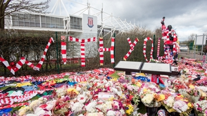 Tributes of flowers, scarves and shirts adorn a statue of Gordon Banks