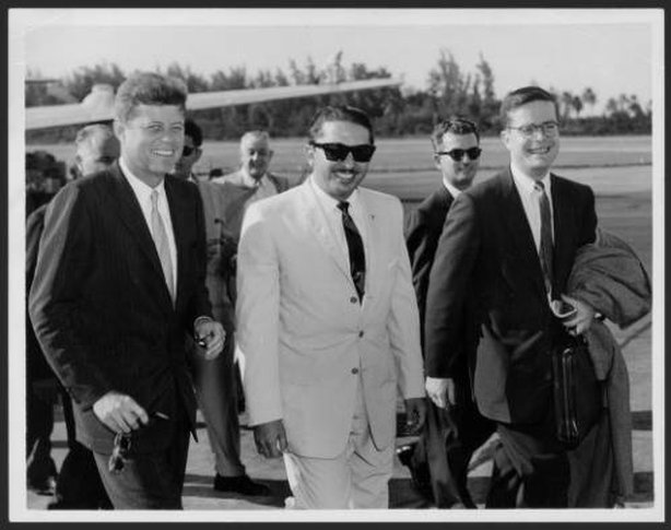 """""""The then Senator John F. Kennedy walking from the plane to the site where he spoke to reporters at the Isla Verde airport on his first visit to San Juan on Dec 15, 1958. At the center Mr. José A. Benítez and on the right a companion of Mr. Kennedy. """" Information: El Mundo, Dec. 15, 1961"""