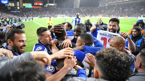 Porto players celebrate their late winner as they beat Roma 4-3 on aggregate to reach the Champions League quarter-finals