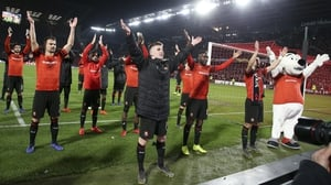 Rennes players, and mascot, celebrate their win against Arsenal in the Europa League