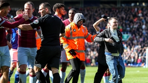 A fan is escorted off the pitch after attacking Jack Grealish.