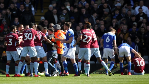 Paul Mitchell (C, black jacket) is restrained after attacking Aston Villa's Jack Grealish on the pitch (right)