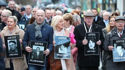 Families of some of the victims are seen during a march in Derry this morning