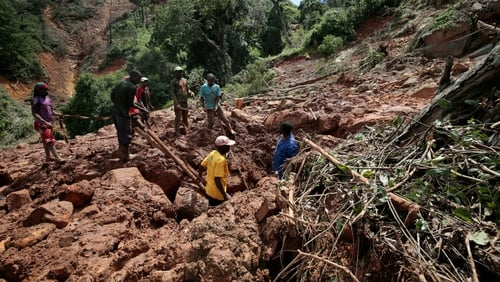 People search for the body of a young man who died after Cyclone Idai hit the Chimanimani in Zimbabwe