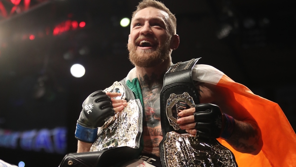 Conor McGregor poses withthe UFC featherweight and lightweight belts in 2016