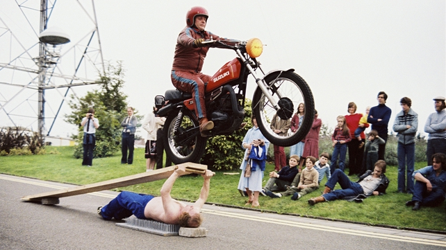 A motorcycle stuntman drives over broadcaster Seán Bán Breathnach, who is lying on a bed of nails, on 'SBB ina Shuí' (1980)