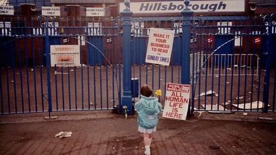 A young girl lays a single flower outside the entrance to Hillsborough Stadium after the stampede which resulted in the deaths of 96 people, Sheffield, 16th April 1989. (Photo by Derek Hudson/Getty Images)