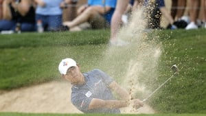 The leader hits out of the sand on his final hole on Saturday