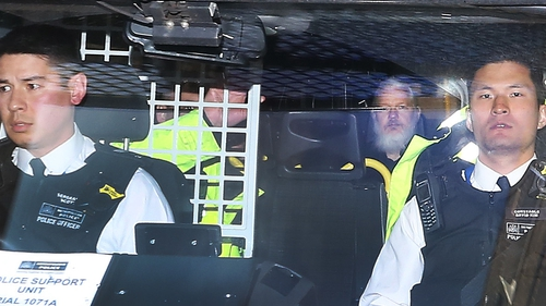 Julian Assange pictured as he left court in London yesterday