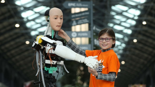 "Emma Mullins, age 9 from the Dun Laoghaire CoderDojo pictured greeting ""KC"" the Robot at the launch of Coolest Projects International"