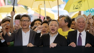 Chan Kin-man (left) and Benny Tai (centre) chant slogans before their sentencing outside West Kowloon Magistrates' Court