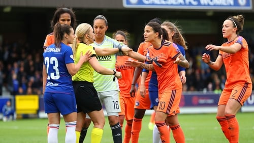 Players surround referee Sara Persson