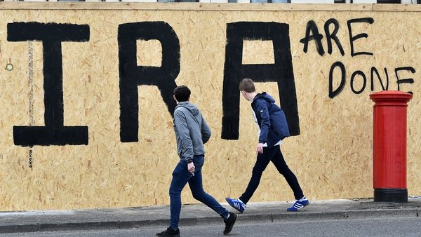 Youths walk past anti-IRA graffiti in Derry the day after journalist Lyra McKee was shot dead. Photo: Charles McQuillan/Getty Images