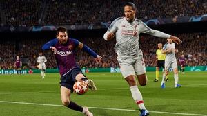 Virgil Van Dijk (R) attempts to challenge Leo Messi