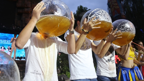 Tourists drink beer out of fishbowls during a beer-drinking competition in Hangzhou, China