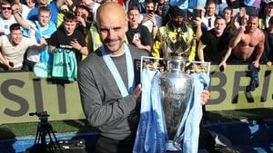 Pep Guardiola poses with the Premier League trophy