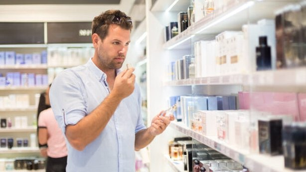 man choosing perfume in retail store