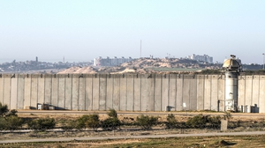 Buildings can be seen in Gaza behind the border wall built by Israel