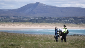 Presiding Officer Carmel McBride and Garda Adrian McGettigan carry a ballot box from the polling station on Inishbofin Island