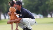 Kevin Na celebrates with daughter Sophia on the 18th green at Colonial