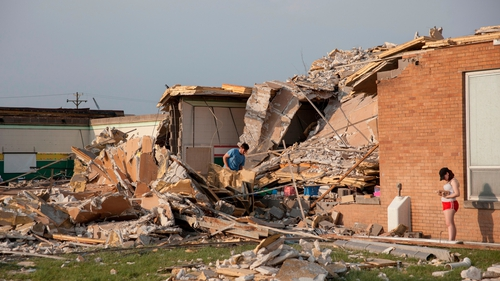 People examine the damaged remains of school in Dayton, Ohio