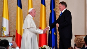 Pope Francis and Romania's President Klaus Iohannis shake hands at the Presidential Palace in Bucharest