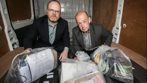 Trevor Birney (L) and Barry McCaffrey retrieve their journalistic material seized by police