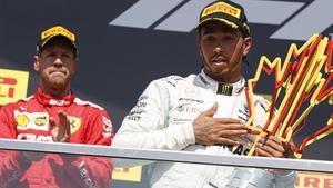 Lewis Hamilton (R) and Sebastian Vettel (L) react on the podium