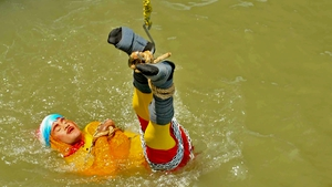 "Chanchal Lahiri, known by his stage name ""Jadugar Mandrake"", is lowered into the Ganges river"