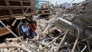 Men pray for their missing relatives at the site of a collapsed building in Preah Sihanouk province