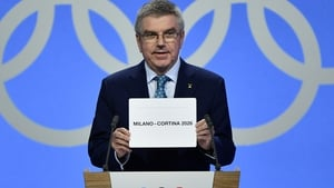 IOC president Thomas Bach shows the card with the name Milan
