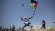 A Palestinian protester throws stones by his slingshot during the clashes near the border between Israel and Gaza in May
